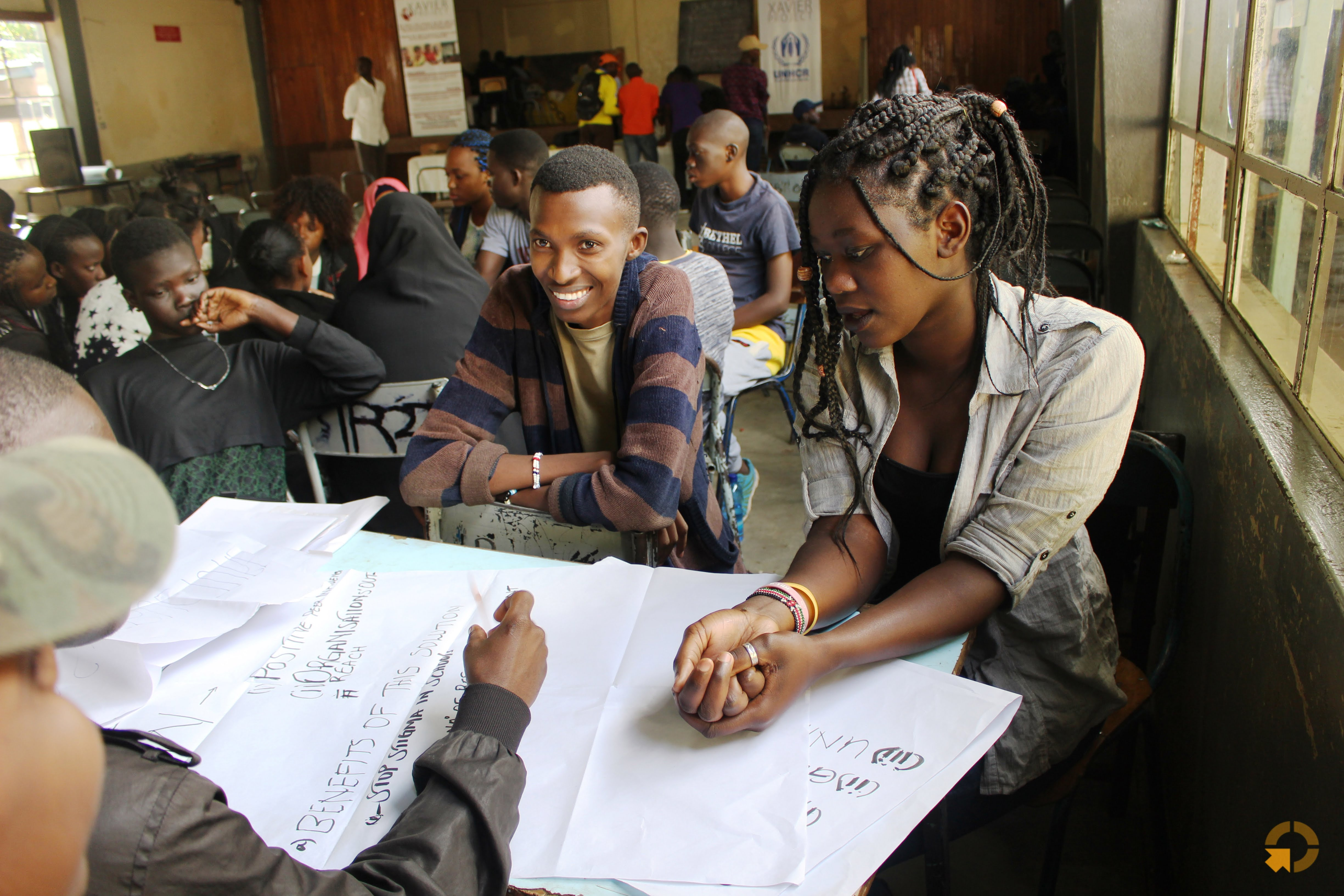 Refugee youth in Nairobi, Kenya, work on a group project to identify hindrances to accessing secondary school and ways to tackle them.