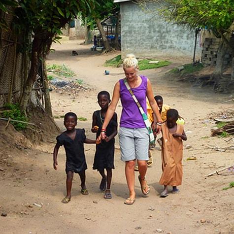 Volunteer Holding Hands With Children in Tanzania