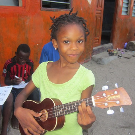Child learning guitar music in Ghana