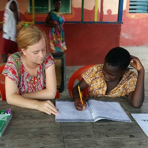 Volunteer teaching child Ghana